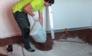 Drobnoziarniste wypełnienie wylewa się na powierzchnię podłogi.